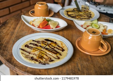 breakfast table setting with banana omelet and fresh mixed fruit salad, with coffee or tea cups in bali homestay