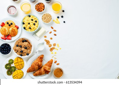 Breakfast table setting with flakes, juice, croissants, pancakes and fresh berries. toning. selective focus