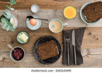 Breakfast table shot from above with bread, egg, coffee, orange juice and jam