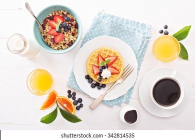 Breakfast table with waffles, granola and fresh berries