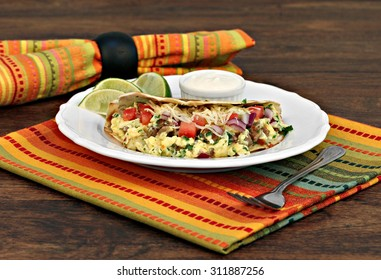 Breakfast taco with scrambled eggs, shredded cheese, chorizo, peppers and onions with a side of lime slices and sour cream.  Selective focus on front of taco.