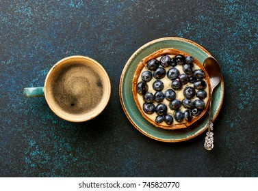 Breakfast with tart and coffee on blue background. Bakery product. Top view.