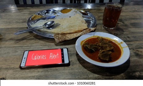Breakfast with thosai, Mutton Curry and sugar free tea with illuminated mobile phone insitu. Is a mixture of calories and healthy diet.
