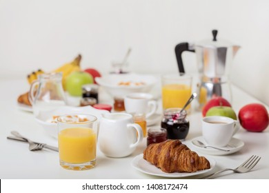 Breakfast time. Croissants and orange juice, jam and honey. Coffee with cream or milk. Fruits - bananas, red and green apples. Ricotta with sour cream and dried apricots. Breakfast on a white table.