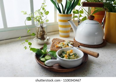 Breakfast time: cucumber and basil egg salad served with bread (wooden plate and marble table)