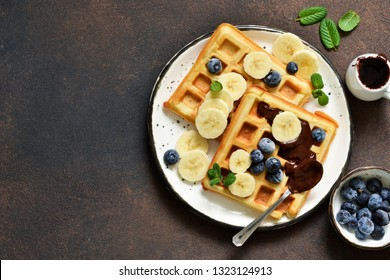 Breakfast time. Homemade waffles with banana, blueberry and chocolate spread on a kitchen table.