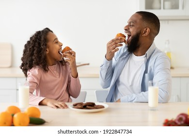 It's Breakfast Time. Portrait of cheerful black little girl and man eating sweet muffin cake cookies and looking at each other, dad and daughter sitting at table in kitchen, enjoying meal with milk