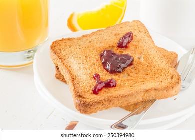 Breakfast - toast with 'I love you' written in jam, orange, juice, tea, white wood background, close up