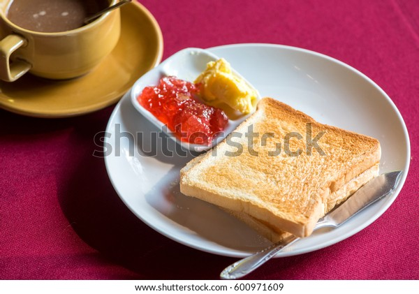 Breakfast, toast, jam, butter and coffee on the table.
