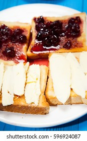 Breakfast, toast with jam and butter on a wooden blue background