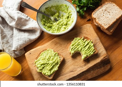 Breakfast toast with mashed avocado on wooden cutting board and glass of orange juice. Healthy vegetarian breakfast