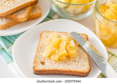 Breakfast - toast with pineapple jam on white wood background