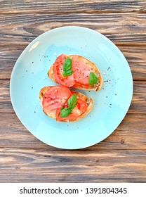 Breakfast toasts with tomatoes and basil on turquoise flat plate. Top view, eating healthy. Home made recipe. Easy meal. Snack or appetizer.Sprinkled with coarse sea salt and pepper flakes.