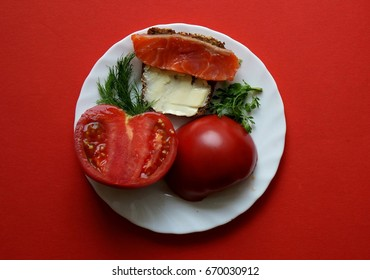 breakfast. Tomatoes and a sandwich with fish