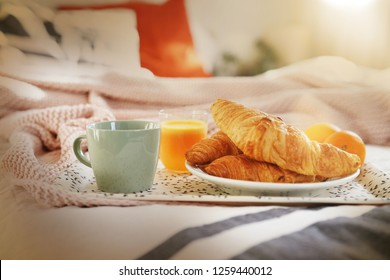 Breakfast tray on bed with fresh croissants coffee and orange juice
