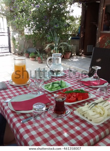 Breakfast with turkish tea, tomato, cucumber and cheese on table outdoor in summer time