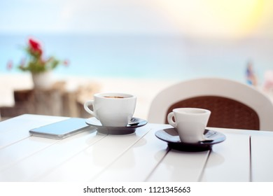 Breakfast for two in a cafe on the beach with two cups of coffee and cell phone