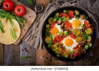 Breakfast for two. Fried eggs with vegetables - shakshuka in a frying pan on a wooden background in rustic style. Flat lay. Top view