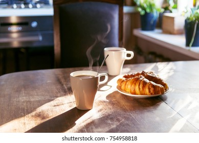 breakfast for two person with cup of hot coffee and fresh croissants