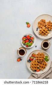 breakfast for two of waffles with honey and berries on light background with copy space