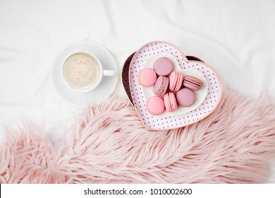 Breakfast for Valentine's day. Cup of coffee and gift box in the shape of a heart with macaroons on bed.