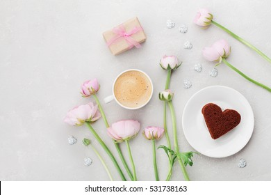 Breakfast for Valentines day with cup of coffee, gift, flowers and cake in shape of heart on gray table from above in flat lay style.