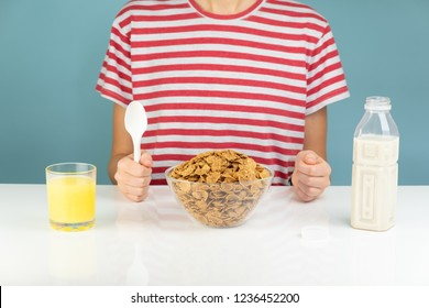 Breakfast with whole grain cereals, milk and juice. Illustrative minimalistic image of healthy vegetarian food on the table and hungry person