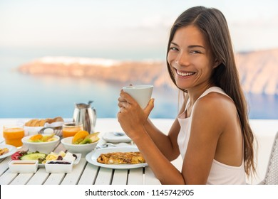 Breakfast woman eating brunch at luxury travel hotel restaurant drinking coffee cup over Mediterranean view from outside balcony. Greek healthy food Santonini vacation.