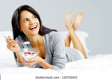 Breakfast woman with yoghurt cereal lying in bed eating a healthy snack with fruit and carefree smile