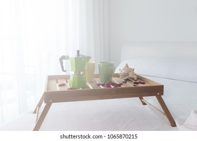 Breakfast wooden tray with coffee percolator and croissant on bed