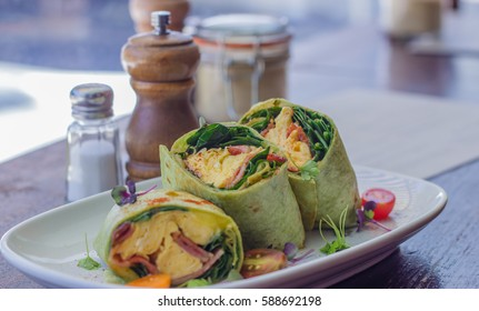 Breakfast Wrap with scrambled eggs,  bacon, cheese, spinach, tomato, barbecue sauce,