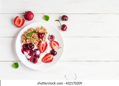 Breakfast with yogurt, muesli and berries on white wooden background. Fresh yogurt. Healthy food concept. Top view, flat lay, copy space