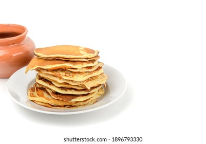 Breakfast.A stack of pancakes in a plate and a pot of honey on a white isolated background.Free space.Space for text, horizontal view.