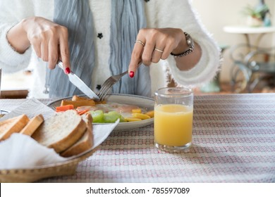 breakfast,first meal of a day,morning food with fried eggs sausage carrot potato and healthy vegetables,woman holding knife and fork for morning breakfast.