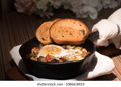 Breakfrast hash in cast iron skillet with sunny side up fried eggs, ham,mushroom, spicy peppers, potatoes, toast, and coffee.