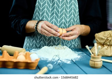 Breaking eggs in the flour. Close up of male hands breaking raw egg over flour. Baker kneading dough for cake. The process of breaking eggs.