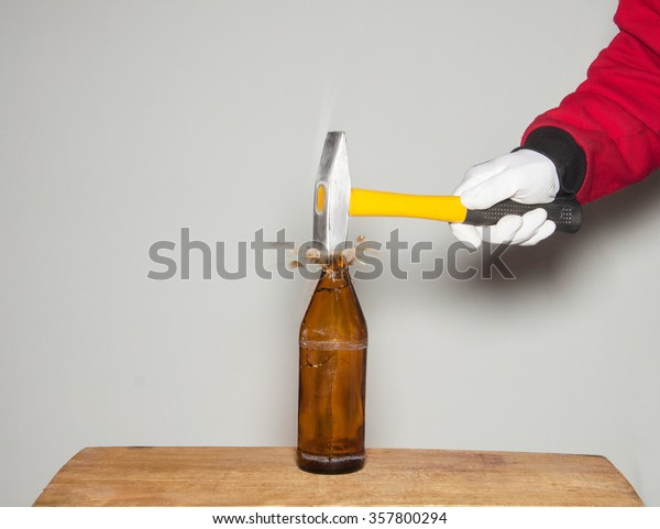 Breaking a glass bottle with a hammer