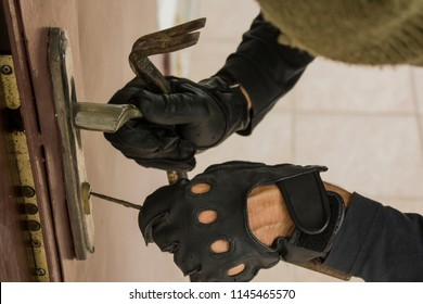 Breaking into house concept. Robber in black gloves breaking door lock.