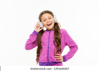 Breaking into a song. Adorable singer isolated on white. Small child doing vocal on song. Little girl singing song for pleasure. Cute kid listening to song playing in headphones.