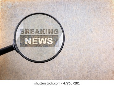 Breaking News. Magnifying optical glass on old paper background