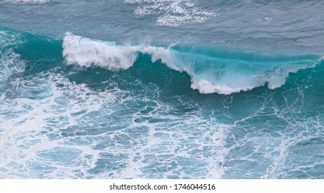 Breaking ocean wave background seen from above, in Bali Indonesia. Marine landscape scene in stormy weather, generating high waves and tides.