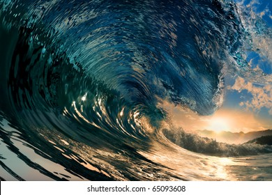 breaking ocean wave falling down at sunset time
