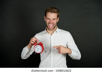 Breaking rules. Time management. Personal schedule daily regime. Alarm clock morning time. Time management skills. Man funny grimace tongue hold clock. Man with beard does not care what time is it.