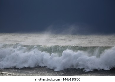 Breaking wave. End of the day light before rain and storm.