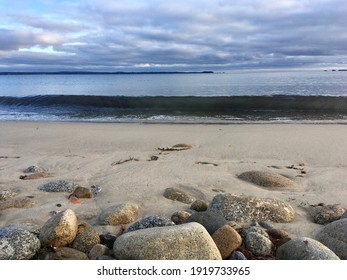 Breaking wave, sand, beach stones, see distant land across the bay