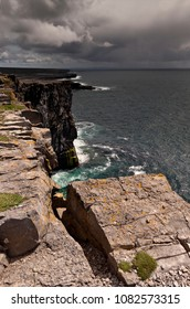 Breaking waves below the dramatic cliffs of the ancient fort Dun Aonghasa (Dun Aengus), in the distance the karst landscape of Inishmore, the Aran Islands, County Galway, Ireland.