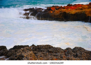 breaking waves at the red rocky coast of Sissi on Crete in Greece