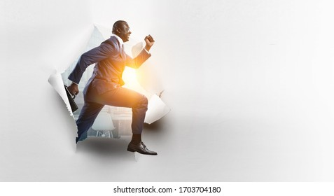 Breakthrough paper hole with a black businessman