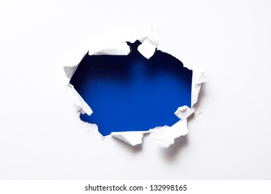 Breakthrough paper hole with blue textured background.