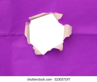 Breakthrough purple paper hole with white background, isolated on white.